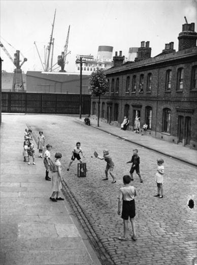 15th August 1938: Children playing cricket in a street in Millwall, east London. A liner on the Thames is in the background. (Photo by Fox Photos/Getty Images)