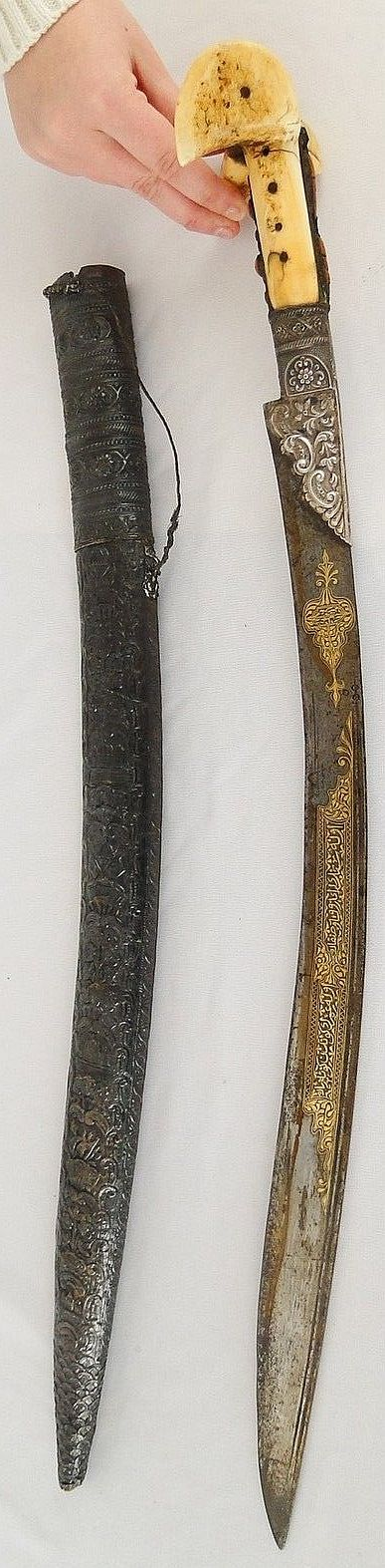"Ottoman yatagan / yataghan, 19th century, the blade has silver engraved mounts and is inlaid in gold and appears to be signed within a cartouche like form on the gold inlay, bone handle, tooled scabbard appears to be silver - silver/alloy over a thin wood two piece core, 29 3/4"" long including scabbard."