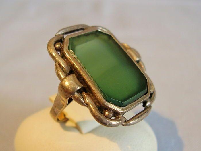 Antieke zilveren ring met groene Agaat van 6 ct.  De ring is gemaakt van 900 zilver en is als zodanig een stempel.Het hoofd van de ring is ingesteld met een fijn gepolijst transparant achthoekige groene Agaat plaat van zeer mooie kleur en kwaliteit. Het is de omlijsting en wordt omgeven door openworked decoratie.Ring maat 52-53 = 17 mm ring band binnendiameterring hoofd 25.1 x 22.7 mmgroene Agaat 19.1 x 14.6 mm = 6 ct.Gewicht 7.0 g.Handgemaakte aan het begin van de eeuw in versleten…