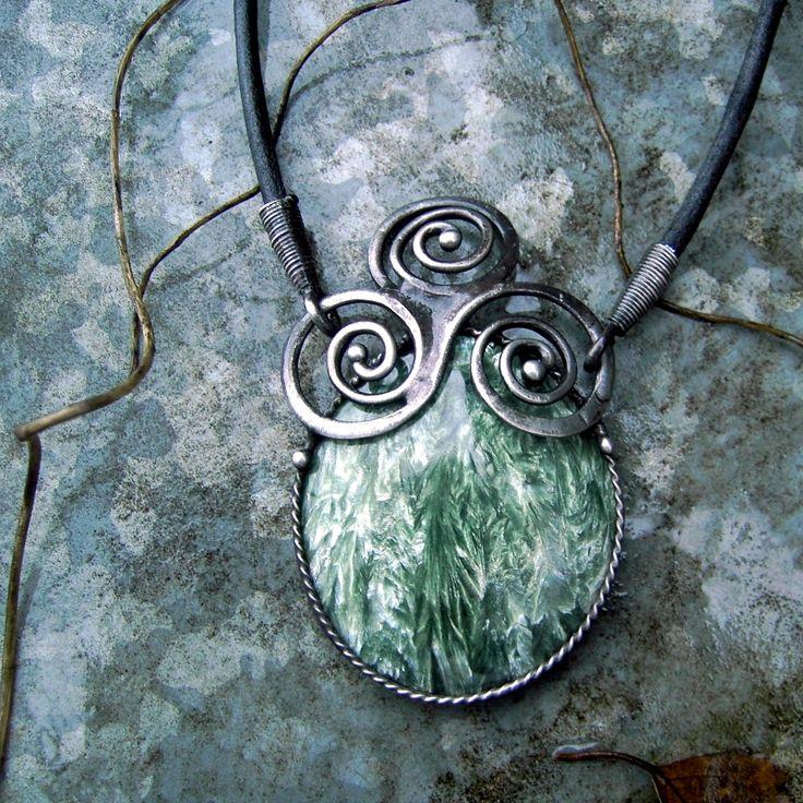 """Echo....v ozvěně zakletá Tento šperk je z nové kolekce """"antika.....přes brány času"""" --------------------------------------------------------------------------------- Šperk je vyroben z cínu, který byl patinován a ošetřen antioxidačním olejem... Vsazeným minerálem je serafinit. Rozměry cínového šperku jsou 7 x 5 cm. Šperk je zavěšen na černý kožený řemínek délky 50 ..."""