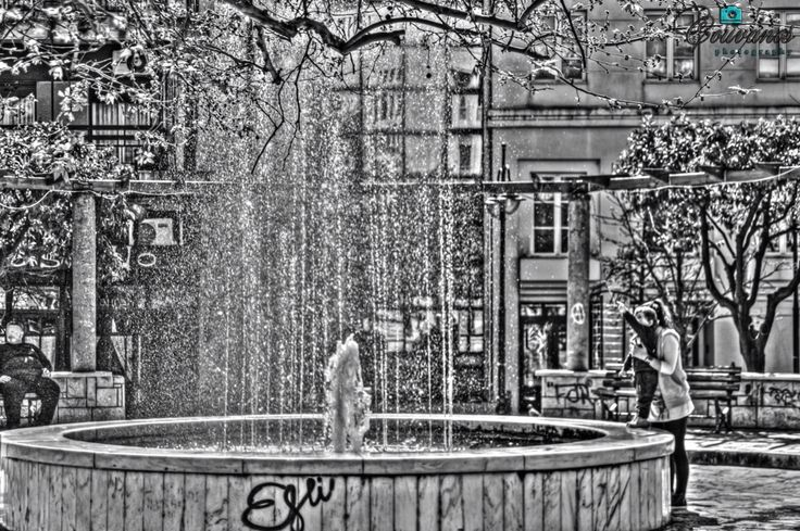 Family! The mother is playing with her son near a fountain...