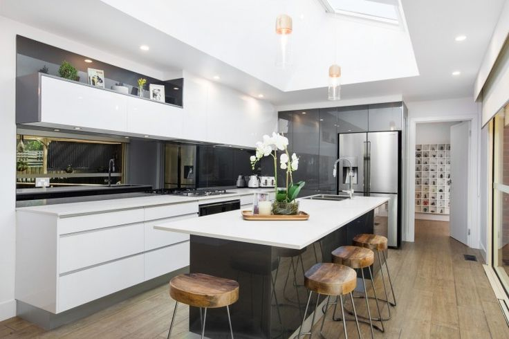 Ultra modern kitchen with black gloss kitchen island and mirrored splashback. Love the huge skylight and pops of timber to bring warmth to the space. See all the photos >>>