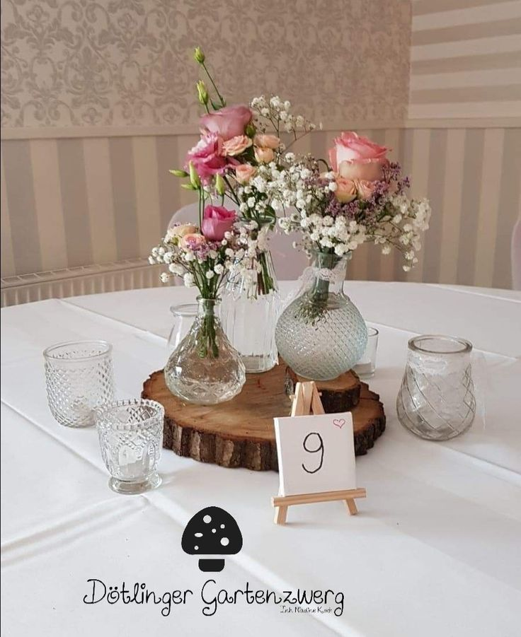 Zarte Vintage Tischdeko, kleine Sträusse kombiniert mit rustikalen Baumscheiben und Windlichtern