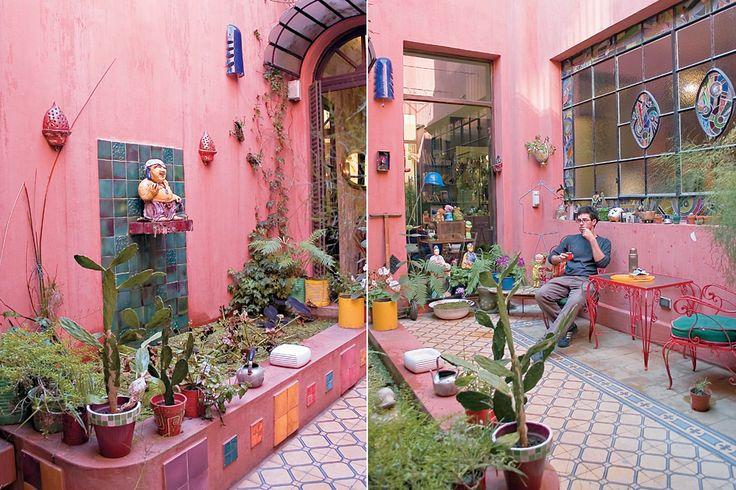 Diez terrazas y patios para tomar ideas  Audaz y original, este patio pintado de rosa fuerte destaca la fuente de pared, coronada por la escultura de un buda que toma mate. Los apliques de pared y el juego de mesa y sillas completan el cuadro. Foto:Archivo Living