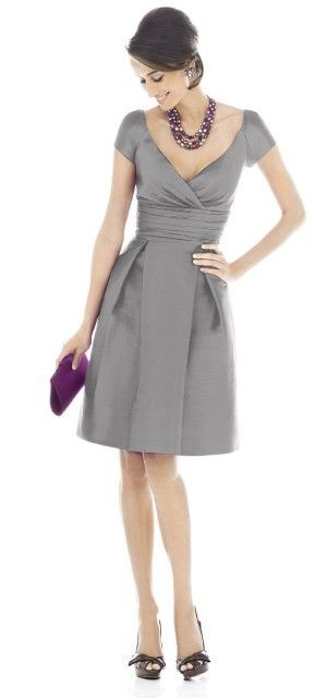 Simple and elegant knee-length dress with purple accessories.