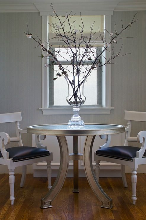 Chic dining room with gray textured walls round silver Greek key table white chairs with black