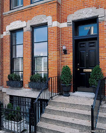 Decorative lintels with horizontal stone band. Transom with house numbers. Black frames & door. Window boxes & urns. Iron rails.  Home Tours: Home Tour: Row House - Martha Stewart