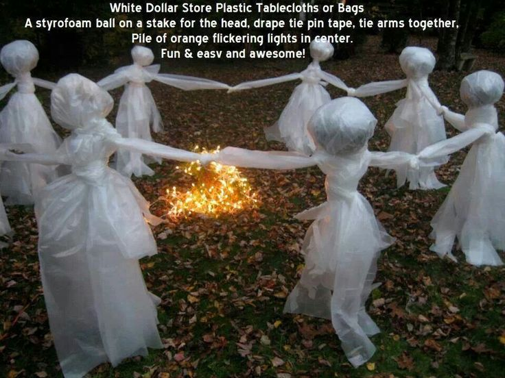 Dollar store white tablecloths or bags, a Styrofoam ball on a stake for a head, drape, tie, pin tape, tie arms together.  Pile orange flickering lights in the middle - awesome.
