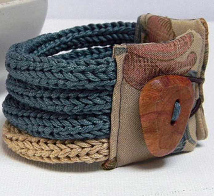 You could easily make this by looking at the design. Single crochet 4 bands, or make them dbl crochet size of your wrist. Sew 2 pcs of fabric over the end w elastic thread to pull over a big button. Adorable.