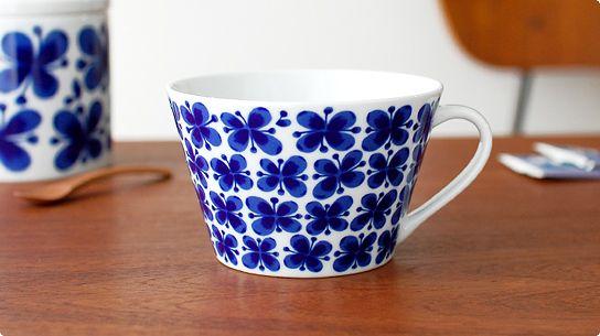 ヴィンテージで大人気の「モナミ」が、新シリーズとして復活。1951年に発表され、1980年代に生産が終了するまでロールストランドを代表するロングセラーとなった大人気シリーズ「Mon Amie(モナミ)」。 現在も現役で活躍するデザイナー自らの手により、2010年新たにデザインされて復活しました。 表面いっぱいに描かれた印象的な深いブルーの花模様はそのままに、 マグカップからプレートまで、今までにない使い途が楽しめる新しいラインナップとなっています。 「Mon Amie」とはフランス語で「友達、恋人」という意味。まさに友人や恋人など、大切な人と過ごす時間にぴったりの、優しくてあたたかいデザインです。 こちらのティーカップは、たっぷり500ml入る大きさ。 カップの底にMonAmieの花模様が一輪描かれています。 カップのまわりの花模様は他のマグカップに比べて小さめに描かれているので、大きめのカップなのに繊細でとてもかわいらしい印象に仕上がっています。 紅茶だけでなく、具だくさんのスープやシリアルなどを入れてもかわいいですね。