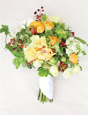 """""""Garden Variety"""" bouquet with geranium leaves, june berries, oak leaf hydrangea, green beans, unripened tomatoes, mini pears, yellow peonies, spray garden roses, and passion vine 
