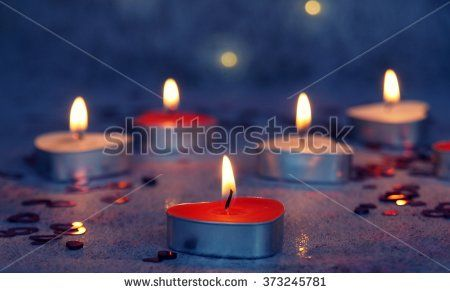 Red and white heart-shaped candles, festive lights - stock photo