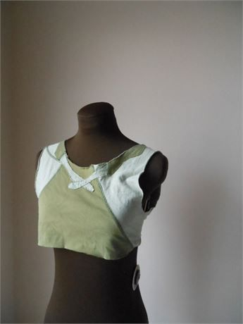 Bohemian moss green crop pixie shirt in pale moss and deeper woodland fairy moss. One of a kind green jersey crop with faux tie applique on front and back neckline. Totally asymmetrical, this one is a fun top layer for camisoles and great for spring and beachy summer adventures. Upcycled green moss jersey top in pale and darker moss green with a darker bodice color and appliques and sleeves in pale moss. Raw edges mixed with appliqued neck details to create a faux tie effect. Fabric is a…
