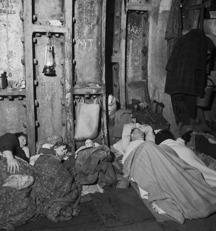 A family sleeping in Liverpool Street Underground Station during an air raid in November 1940. I love that the doll has a bed!