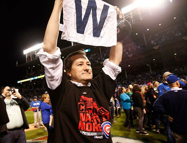 Chicago Cubs owner Tom Ricketts holds up a sign after after winning Game 4 in baseball's National League Division Series against the St. Louis Cardinals.