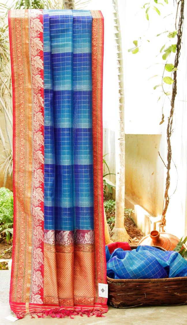THE CHECKERED SHADES OF BLUEBENARES KORA WITH CONTRASTING RED BORDER AND PALLU THAT HAS INTRICATELY WOVEN GOLD AND SILVER ZARI FLORAL BORDER THAT MAKES THE SARI SUBLIME.