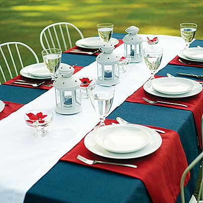 """Festive tabletop for the Fourth - solid bottom tablecloth, then runners criss-cross the table for each """"placemat"""". Change the colors of the runners for other holidays."""