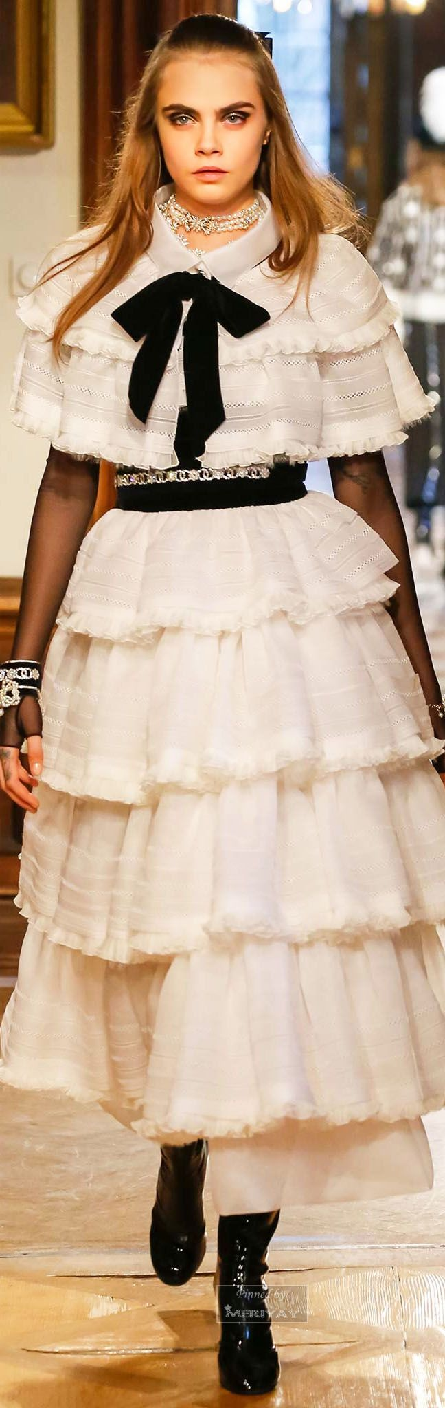 Chanel.Pre-Fall 2015. I quickly noticed the fabric and tiered appearance and thought it resembled the mid 1910s evening wear look. Such evening wear at this time held a slightly higher natural waistline with a fuller skirt made from tiers of ruffles or layering of different length fabrics. Sheer and lace were other components used in such decade evening wear. This recreated design holds similar characteristics and qualities yet is current and wearable in this era.