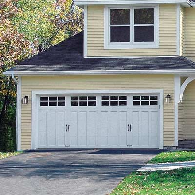 A double-wide carriage door with divided-light windows and recessed paneling turned an eyesore into a focal point. The extended roof line is accented with a decorative bracket on one side. 1354 GARAGE DOOR