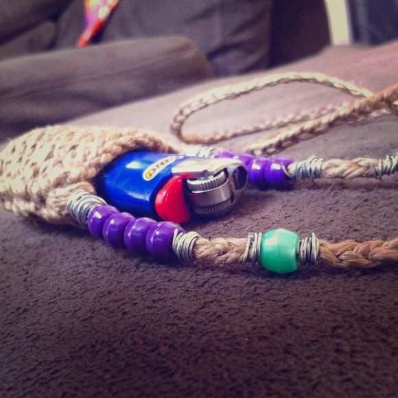 HEMP LIGHTER HOLDER 🔥🚬 This is one of the many eclectic lighter holders I make.  It has such a HIPPIE feel to it I knitted the body and braided the necklace with hemp. It has pretty bold purple and glossy green beads along the necklace, each surrounded by silver metal coiled around the necklace where the hemp is braided. This is a great piece for smokers,  you'll never loose your lighter this way. Hang it around your neck or on your rear view mirror. These come in different styles. Message…