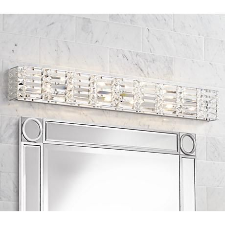 A glamorous 6-light bath fixture in a chrome finish with clear crystal accents that produce a soft glow when turned on.