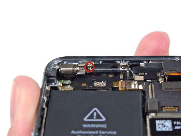 3. Fjern 1,7 mm Phillips-skruen som fester vibratoren til bakdekselet.