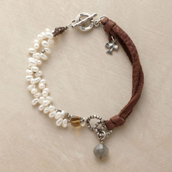 A double strand of freshwater pearls runs between turrets of cognac quartz and smoky quartz beads and attaches to a leather cord with two beaded...