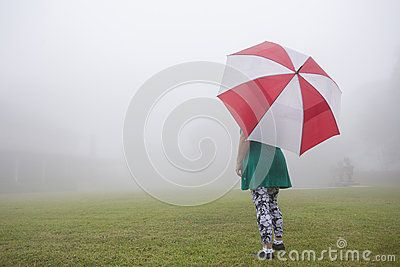 Woman with umbrella stands front of home across lawn through cloud mist.