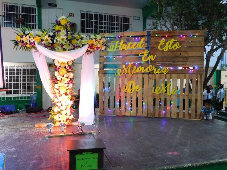 """Decoración del patio del colegio para la Santa Cena o la Cena del Señor un viernes de tarde. Puedes observar que la cruz esta cubierta en su totalidad de flores acompañado por un manto de tela blanca translucida y unas focos para dar más dramatismo el evento. Además de una pared de palets con la frase """"Haced esto en memoria de mi"""" con luces navideñas para darle un pop de color."""