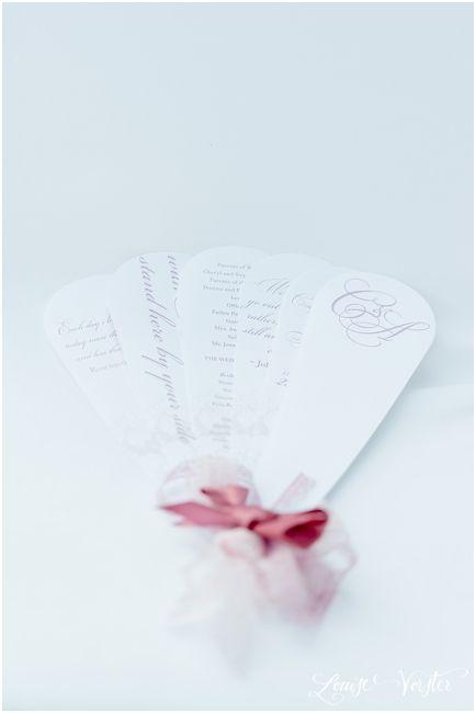 Pink wedding program in the shape of a fan.