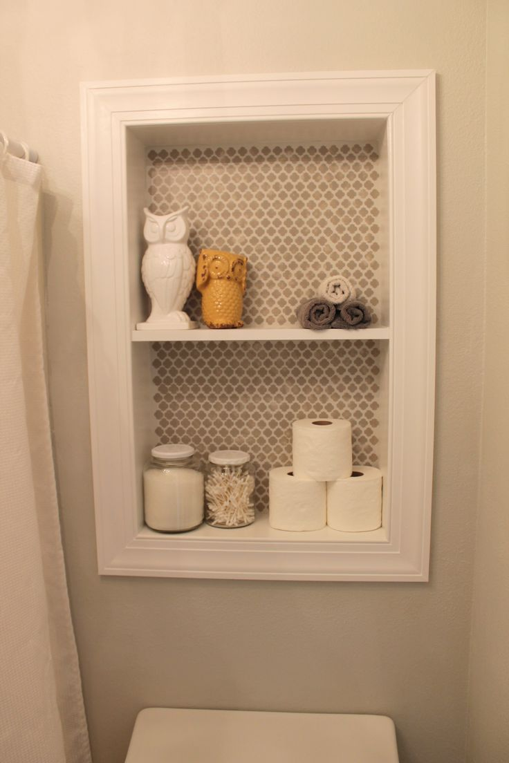 DIY built-in shelves for small bathroom storage. Cut out sheet rock between the studs centered above the toilet. Frame in a box out of 2x4s plus shelf. Add trim, sand, calk, primer and paint. I also added a stencil to just the back for interest, and blotted the wet paint to get a weathered look. The jars are re-purposed pickle jars :)