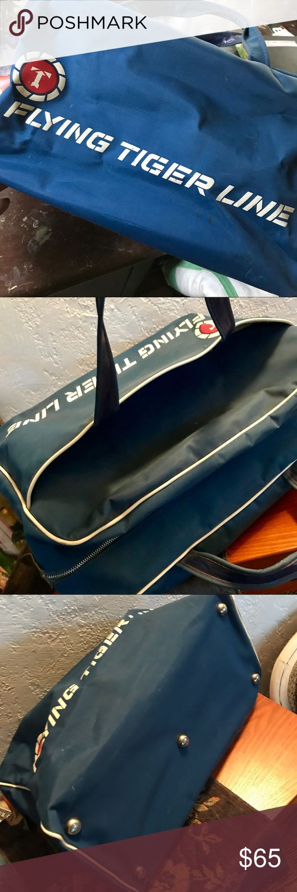 """Vintage Flying Tiger Line airline carry-on bag Original vintage/retro bag, from the 1970s as far as I can deduce, though possibly 1960s. In good used condition; metal zipper, one exterior pocket, clean lining, metal feet on bottom. A few minor marks and scuffs but no structural damage. Approx. 9"""" high, 15"""" long. Width tapers from 6.5"""" at bottom to 5"""" at top.  Great unique piece for overnight travel or daily handbag. Flying Tiger Line Bags Travel Bags"""
