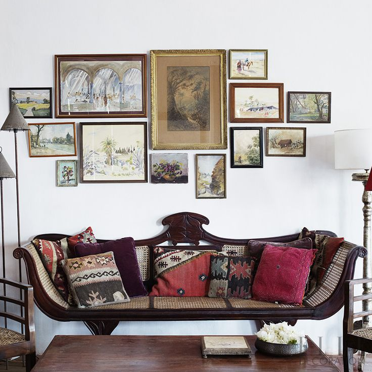 GREAT JOB WITH THE ART WORK!    This globetrotting jeweller has collated treasures from her travels to create a colonial feel, fusing influences from France, India and Africa in her 100-year-old Goan home. Here, she has hung framed artwork to create a feature wall above this vintage Indian sofa