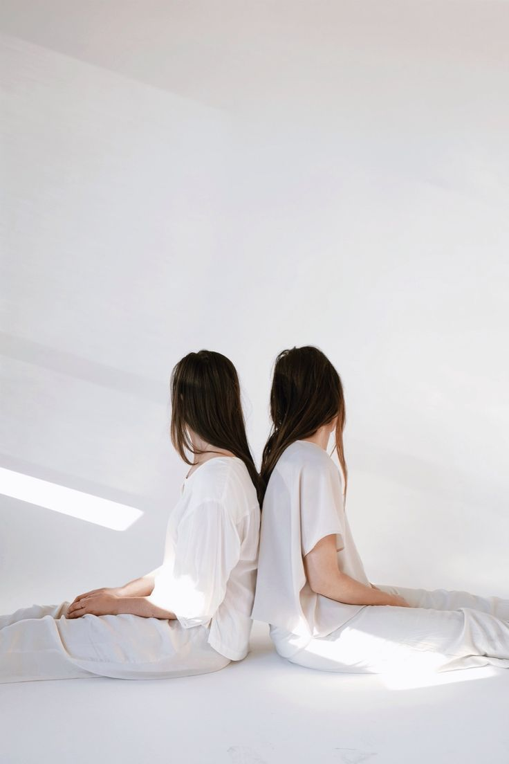 Couple of girls in white, sitting back to back