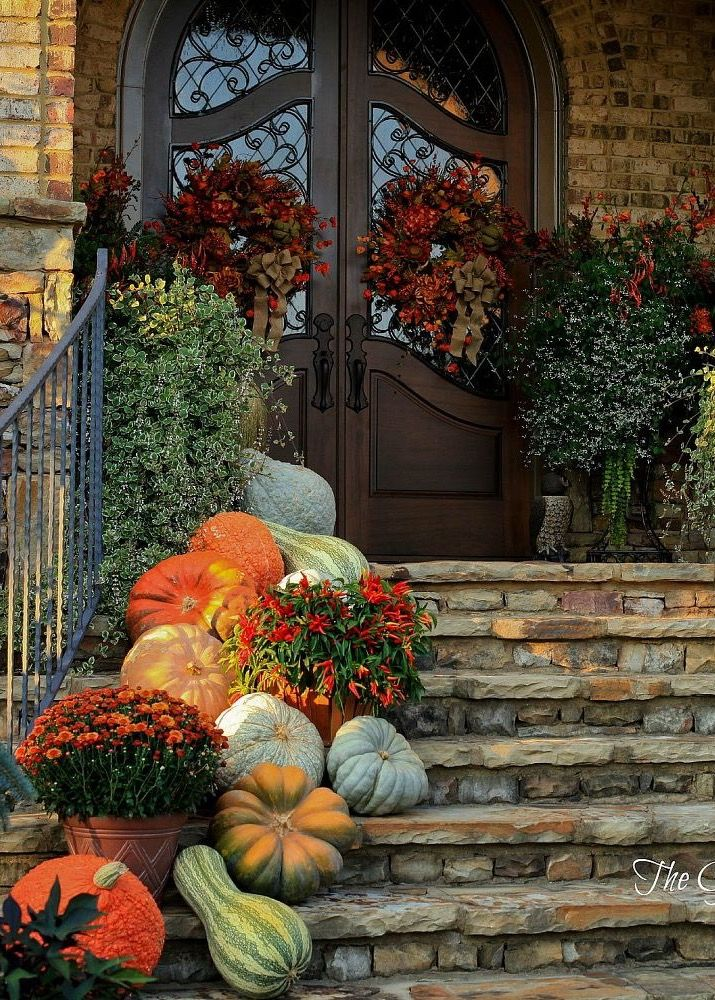 Charming Old World style entrance beautifully decorated with mums and pumpkins and squashes for FALL