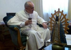 Pope Francis enjoying Yerba Mate while seated next to a statue of the Virgin of Luján.