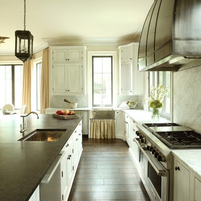 Modern cottage kitchen features iron and glass lanterns illuminating expansive island topped with honed black countertops, single bowl sink and stainless steel dishwasher across from stainless steel hood with iron forged straps over Wolf Range with double ovens.