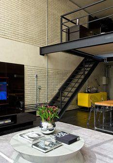 Zářivě žlutá komoda ve vstupní chodbě vytváří v černo-šedém interiéru žádaný kontrast