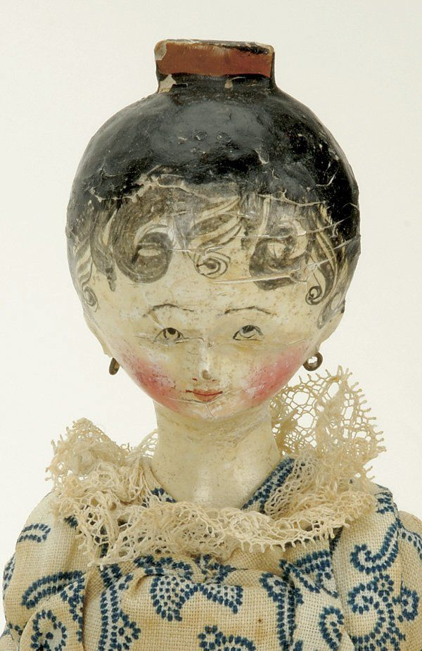 """England, ca. 1830, early wooden doll with carved tuck comb, black painted hair with tendrils, pierced ears, painted features, fully jointed body, original cotton floral dress with yellow pantellets Size: 12.5"""" t."""