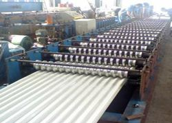 Roofing Sheet Roll Forming Machine with hydraulic uncoiler, sheet feeder, roll form structure, hydraulic post-cutting unit, and hydraulic station with control panel. The sheets shaped by this line are strong and long-lasting with elevated ribs