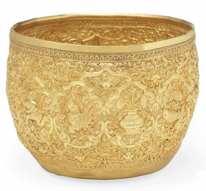 A GOLD-REPOUSSÉ BEGGING BOWL   THAILAND, CIRCA 1900   Rimless, of slightly rounded profile, on plain base, the gold repoussé decoration with signs of the zodiac within cusped medallions against dense scrolling foliated ground, the base with a kinaree within a roundel  4in. (10.5cm.) diam.  [I'd really like to know the story behind this one.]