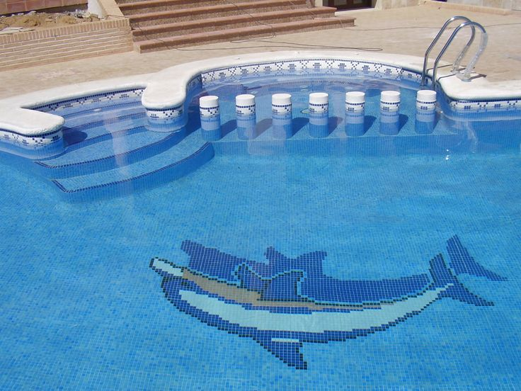 Piscina con forma de riñón con spa adosado y motivo de delfín en el fondo.