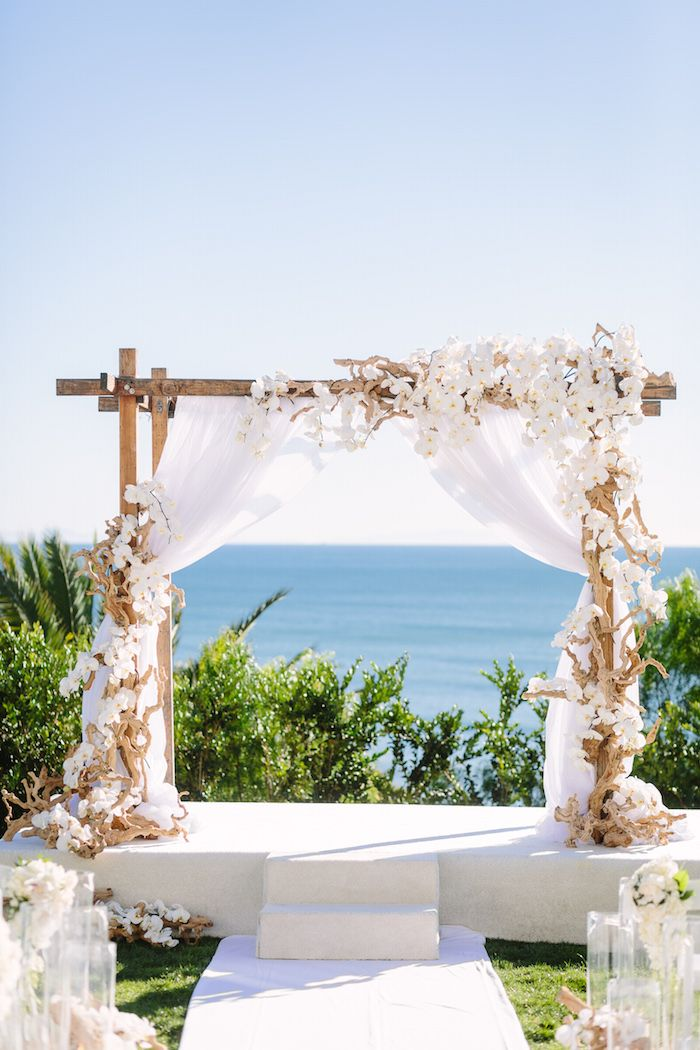Beach Ceremony with White Floral Décor | Photo: Brian Leahy Photography. View More:  http://www.insideweddings.com/weddings/beachy-southern-california-ceremony-winter-wonderland-reception/877/