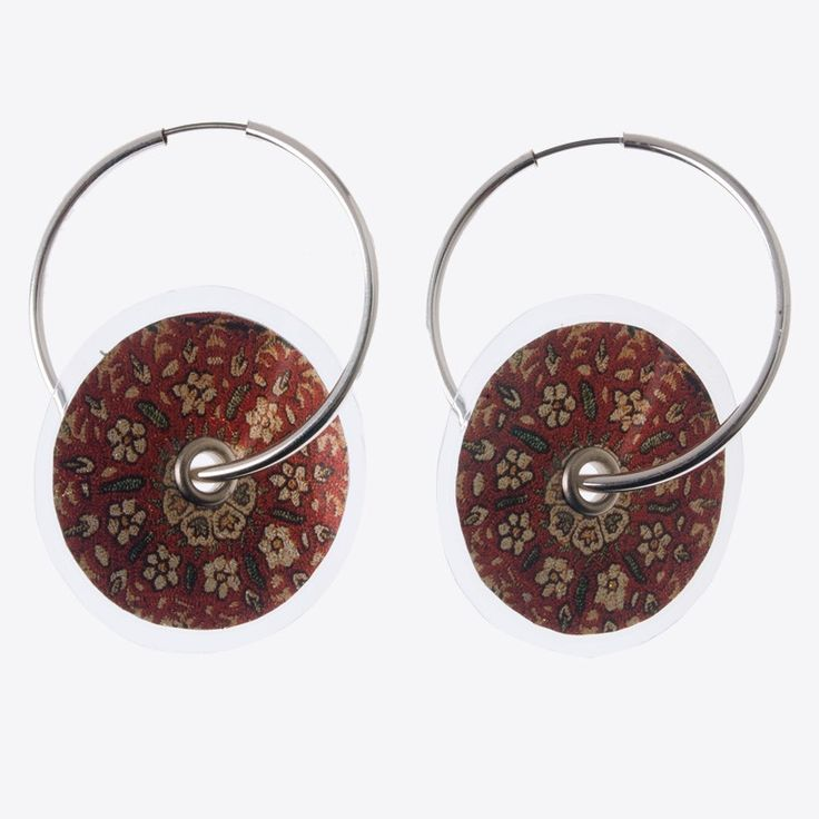 Digitally printed earrings with motifs of traditional Greek embroidery. Made of silver leaf and plastic film. Stamatis Zannos designs jewels inspired by the contemporary Greek civilization as it is showcased in museums. Zannos has presented his work in several venues, including the Benaki Museum in Athens.