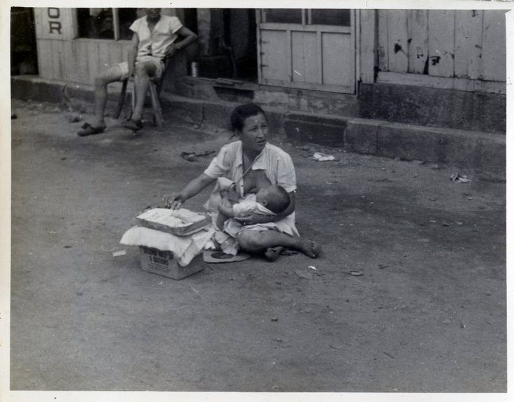Mother with baby selling cigarettes 1948