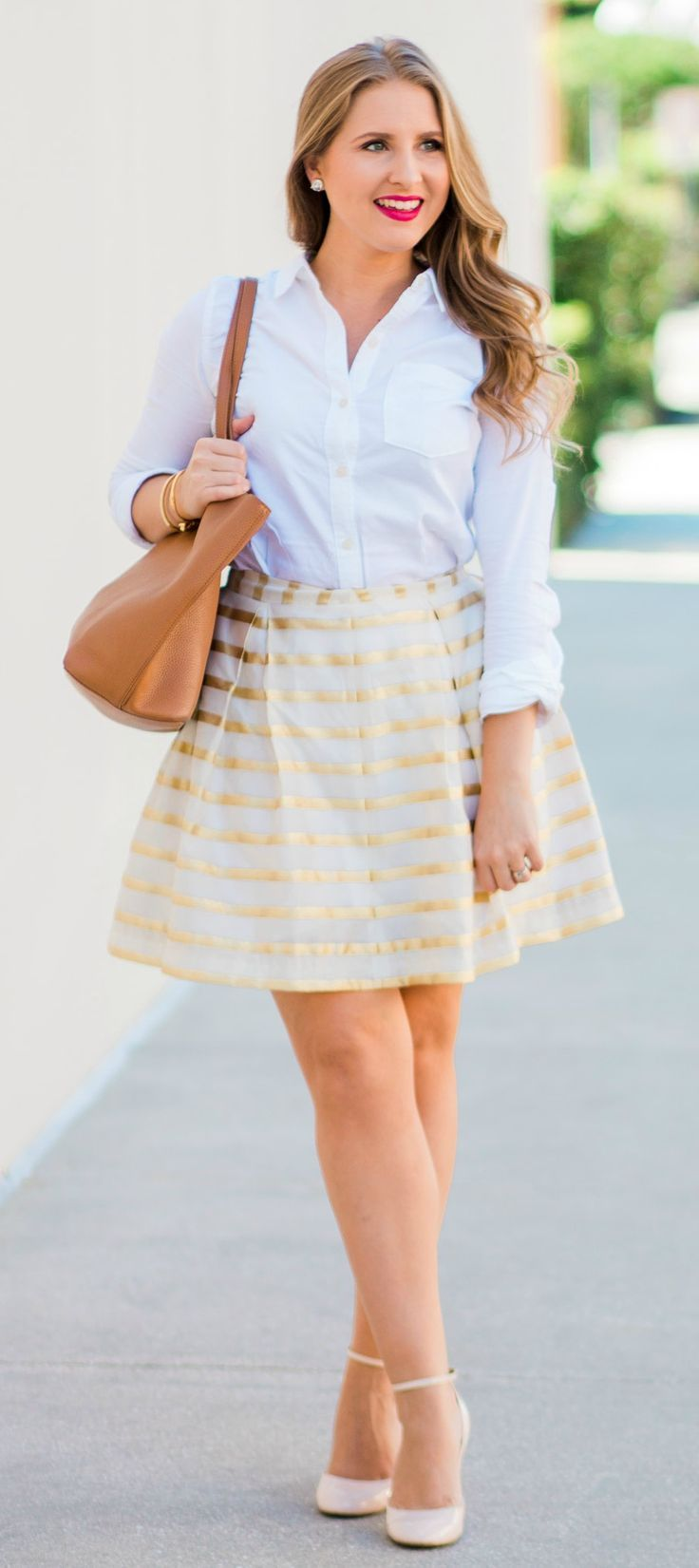 A preppy outfit idea featuring Lilly Pulitzer Kylie skirt in gold and white stripes, Abercrombie classic white button-down Oxford shirt, Charlotte Tilbury The Queen lipstick, Kate Spade clear stud earrings, Tory Burch Perry Tote in cognac, Banana Republic nude pink block heel pumps, Kate Spade pave bow bangle bracelet, and Taudrey engraved gold bracelet styled by fashion blogger Ashley Brooke Nicholas in Orlando, Florida | preppy fashion, prep fashion, prepster, preppy inspiration, buy me…