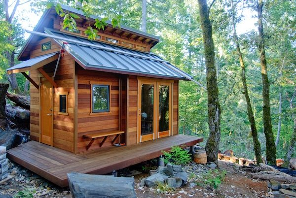 Fantastic design utilizing one steep roof for solar energy, and a lovely little awning plus double doors.  Lovely wooden exterior.  Very unique Tiny House.