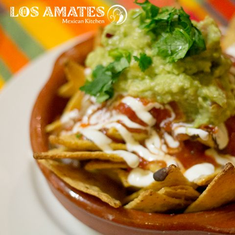 Nachos Los Amates: Corn Chips with Salsa Roja, frijoles negros, cheese, guacamole and sour cream.