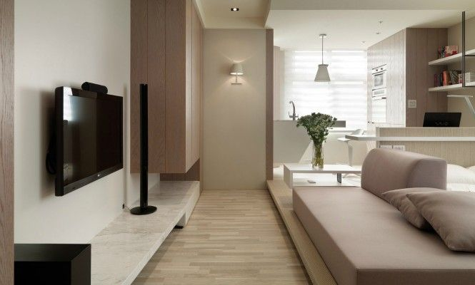 A low-level entertainment unit runs well below eye-level to keep the flow of space unobstructed in the entryway to the apartment. The home gadgetry has been selected for its flat and thin dimensions.