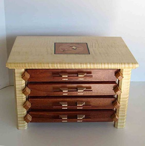 """Jewelry box made from Curly maple and Macacauba inlaid into the wood with the black trim. The finish is a boiled linseed oil and satin lacquer and the drawers are lined in felt. The drawer pulls are hand made Top two drawers have wooden dividers. 14"""" long, 9"""" high and 12"""" deep"""
